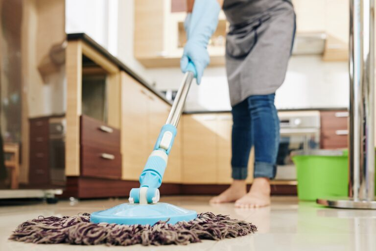 Housewife mopping kitchen
