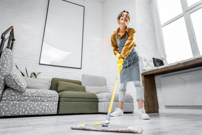 Housewife portrait with a mop indoors