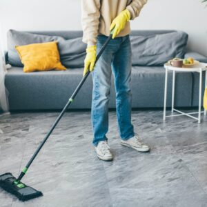 Man washes the floors with a mop in room.