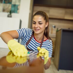 Portrait of beautiful girl wiping dust from table while wearing gloves.