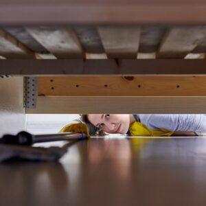 Woman cleaning floor under bed using flat wet mop.