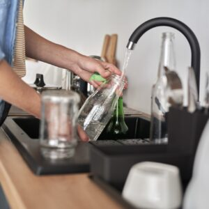 Woman washing white glass bottles for recycling